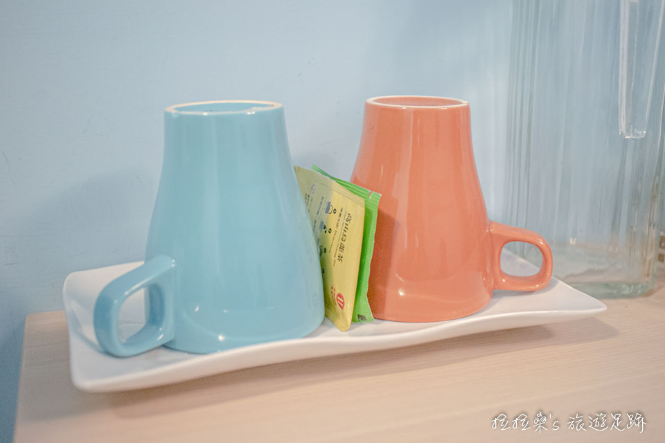 台中逢甲美宿館房間牆上的木頭架子,則放著茶杯、水壺、快煮壺、浴巾、吹風機